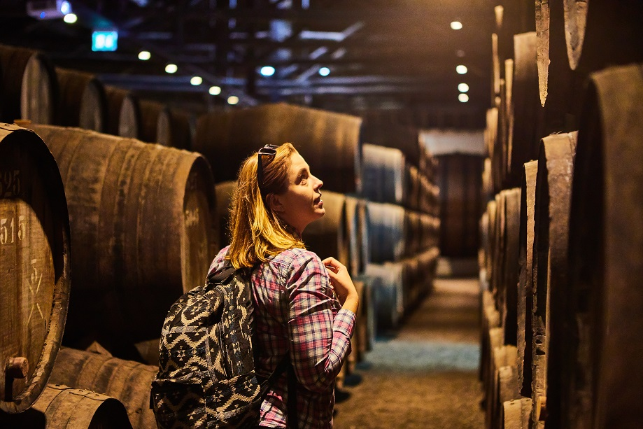 Women on a wine tour looking at wine barrels at a winery.